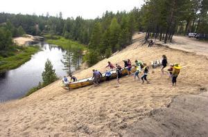 Den stora kanoten är ett rejält åbäke som man hjälps åt att skjuta nerför den höga sandstranden vid Vinströmmen för att få ner den i ån.