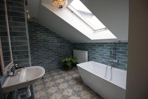 Ett rejält ljusinsläpp i snedtaket har det här nyrenoverade badrummet på brukshotellet.