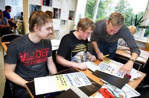 Nikolay Zhurbenkov och Robin Säve pluggar trafikskyltar med utbildningsledare Peter Nilsson.