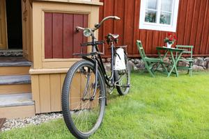 Faster Annas gamla cykel står lutad mot gammelgården. Hans-Olof har rustat upp den så att den rullar perfekt.