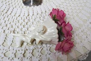 Pynta bordet med det du har hemma. Den här ängeln, som bär ett fång rosor, är egentligen en väggprydnad. Kolla även bland julsakerna eller klipp röda hjärtan av kraftig tyg och strö ut över bordet.