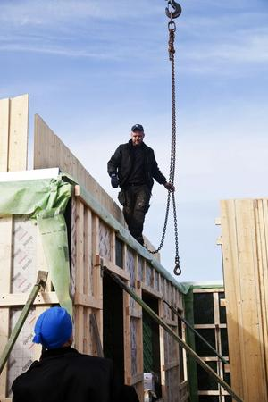 Jan Mård kopplar kättingarna så att den stora kranen kan lyfta väggdelen på plats, medan brodern Kim väntar på klartecken.