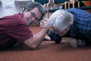 Seved Bornehed och Jern Hamberg demonstrerar hur det såg ut när sjukhusclownen och överläkaren bröt arm på golvet en gång i Akademiska sjukhuset i Uppsala. Överläkaren konstaterade att det var den bästa nyckel han hade fått för att kunna inleda ett samtal med den svårt sjuke pojken.