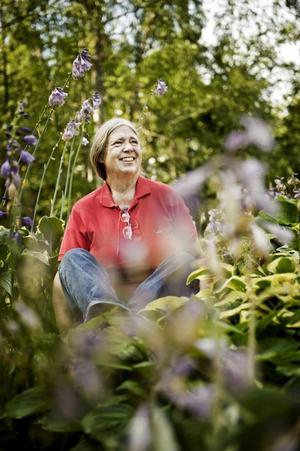 Birgitta Berglund började anlägga en ny trädgårdslund för något år sedan. Här har hon satt sig i ett stenparti på vägen till den. Det domineras av funkiablad så här års.