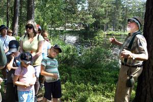 Guiden Åke Pettersson berättar om Fagertärn för ett 30-tal nyfikna, bland annat Pernilla, Emil och Malin Borg.