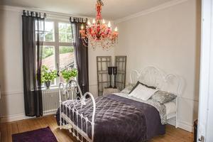 Annat sovrum med kul kristallampa och en underbart söt sängram.