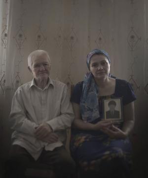 Paret visar ett porträtt av sonen, bortförd sedan flera år. De fick en påse med hans likdelar i, men mamman hoppas fortfarande att han ska vara vid liv.