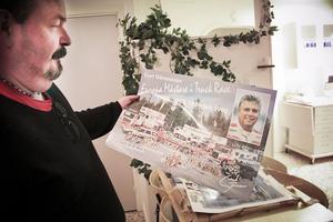 Lars Beck håller i ett plakat som visar Curt Göransson med sina tävlingsfordon.
