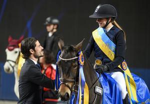 Prins Carl Philip delar ut prisbuckla till Mathilda Bohlin på hästen Dilba som vann ponnyhoppningen Prins Carl Philips pris under Sweden International Horse Show i Friends Arena i Solna.
