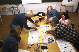 Ann Jonsson visar resvägen på en karta över Moldavien. Bredvid henne sitter Xenia Hildén och på andra sidan bordet lyssnar Lena Hedström Källman, Anna-Maria Eriksson och Kerstin Jonsson.
