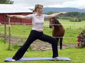 Triangelposition. Birgitta Järnåker gör yoga. Hästen New Dawn i bakgrunden.