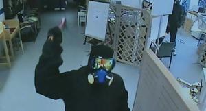 Den trio som rånade Handelsbanken i Vansbro bar liknande kläder och masker som rånarna i Värmland. Här krossar en av rånarna en av bankens övervakningskamera med en kofot.