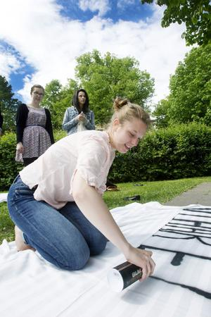 Jenny Edlund Ängskog fixar banderollen åt SP3AK. Eleverna har lagt över 500 kronor per person för att kunna åka flak hela kvällen.
