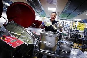 Kokerskan Märtha Edlund häller upp den persiljestuvade potatisen som ska serveras med isterband i tråg.