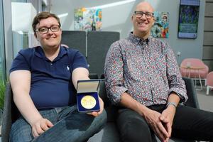 Johan Fohlin visar upp medaljen han belönades med för att ha räddat livet på sin arbetskamrat. Det var hans chef Kjell Persson, till höger, som nominerade honom och Staffan Berg