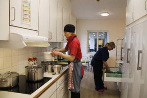 Kocken Lisa Rydbäck och Sara Karlsson i omvårdnadspersonalen lagar dagens lunch. Kockens uppgift är att samordna matlagningen i de olika köken. Själva matlagningen står i huvudsak omvårdnadspersonalen för.
