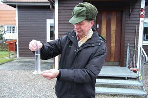 Per-Ove Johansson visar hur han använder sig av ett millimeter mått för att mäta nederbörd.