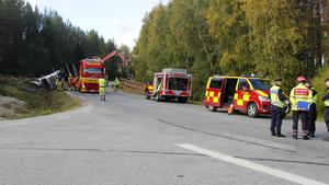 Räddningstjänsten arbetar under timmerbilsolyckan.