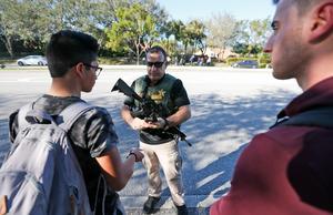 En polis pratar med elever vid skolan efter att skjutningen har ägt rum.