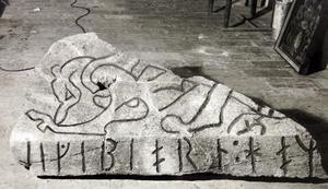 Arkeologerna lyckades foga samman ett tjugotal delar av den runristade stenhällen. På kanten står det