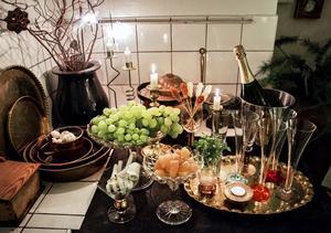 Ur glasskålen på fot serveras överdådigt med druvor. Det bjuds på syltad ingefära medan tomteblossen sprakar över spisen.