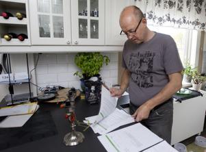 Ove Lindeberg går igenom energiavtalet hemma i köket i Hudiksvall. Han har pressat ned sin årsförbrukning rejält och upplever att en morot nu har tagits bort av fjärrvärmeleverantören Värmevärden.