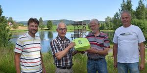 Flankerade av livräddarna Magnus Knuts och Nils Berglund överlämnar Rolf Pellas en hjärtstartare till  Vastannor-Smedby bystugeförenings ordförande Sven-Åke Petters.