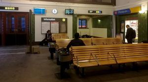 De morgonpigga resenärerna värmer sig i väntan på 06.06-tågets avgång. I hörnet utanför toaletterna sover någon på kartonger och tidningar.