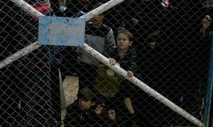 Barn tittar genom gallret inifrån flyktinglägret al Hol i nordöstra Syrien, där långt över 70000 människor från tidigare IS-kontrollerade områden har samlats Foto: Maya Alleruzzo/AP Photo