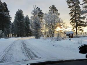 Backe ligger inbäddat i milsvida skogslandskap. Vägen på bilden leder in i byn, men bilen är på väg ut.