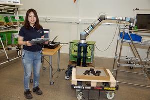 """Förre KTH-studenten Xiaomeng Zhu från Kina har varit på Scania i ett år och arbetar som projektingenjör på Smart factory lab. Här är det en kameraförsedd """"seende"""" robot som plockar pedaler till trampbilen som ska tillverkas och lägger dem i en låda som sedan via en automattruck kör lådan vidare till monteringsstationen."""