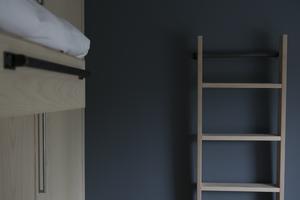 Stegen som leder upp till extrasängen går lätt att flytta så att den  inte är i vägen för garderoben. Istället blir det en snygg inredningsdetalj.