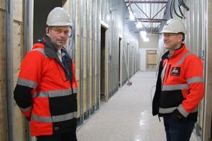 """Thony Eriksson och platschefen Jan """"Putte"""" Almgren på Aros bygg visar byggbörjan av korridoren på vårdcentralen där mottagningsrummen ligger."""
