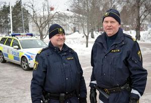 Kommunpoliserna Erik Gatu och Hasse Ryberg på plats i Mockfjärd. I bakgrunden ses Hedens skola, där kommunen idag har SFI-undervisning och uppdragsutbildning.