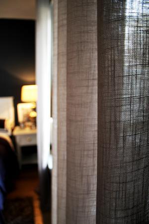 Gardinerna i sovrummet är inte i linne, men det ser ut så.
