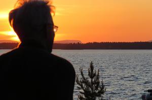 Bruno Svensson, Söderhamn, inväntar solnedgången på årets längsta dag. Platsen är Humlegårdsstrand och fyra mil åt NV ligger Blacksås med sin karaktäristiska branta profil bakom vilken solen snart kommer att halka ner. Klockan är 22.24.