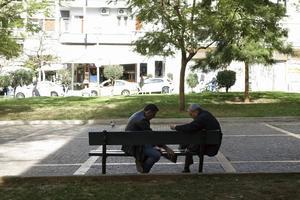 Två män, en bänk och en kortlek bakom Metropoliskatedralen.   Foto: Mikael Nilsson/TT