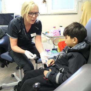 Vårdvardag på hälsocentralen Hälsopartner. Undersköterskan Lisa Landström tar blodprov på Abodi Alaleh.