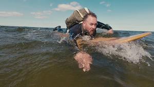 En stillbild ur en av Ica Bommens egna reklamfilmer. Handlaren Peter Hermertz surfar ut till kunderna för att leverera mat. Foto: McGarrett.