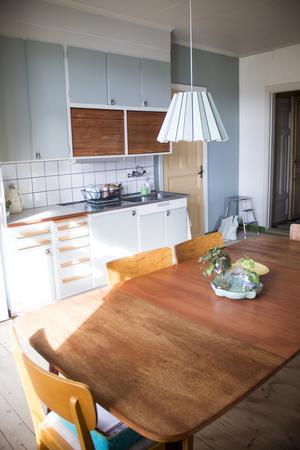 Funkisköket med snabelhandtag och jalusiluckor över köksbänken har de renoverat med tidsenlig kulör.