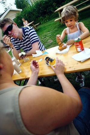 Astrid och Annie Kallå äter glass tillsammans med Birger Klevestedt på uteserveringen.