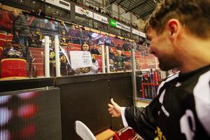 Johan Alzén stoppas av några unga supportrar på läktaren som vill klunsa om hans klubba.