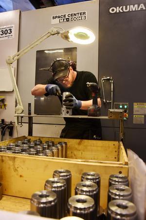 Robin Löfgren  med en uppsättning sviveltappar som ska bearbetas. I bakgrunden en av flera fräsmaskiner som används i maskinbearbetningen av gjutna metalldelar från kunder.