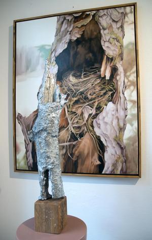 Oljemålning och tennskulptur. Fågelbo i den håliga trästammen, och gren i sönderfall.
