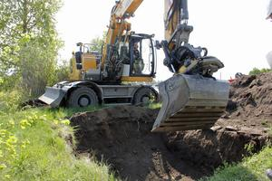Med hjälp av grävmaskin, här rattad av Jesper Sangefors, tar sig arkeologerna ner till 1600-talets marknivå.