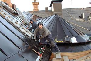 Mesta jobbet består i att dubbelfalsa, alltså vika plåtkanterna två gånger. Gustav Lind och Marc Björklund vid en trapphus-kupa i en ränndal på fastigheten Verdandi 9.