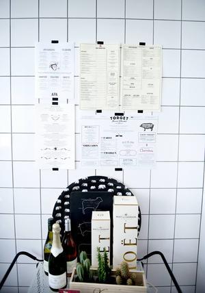 På den kaklade väggen i köket sitter prints på menyer från några restauranger som hon har besökt.