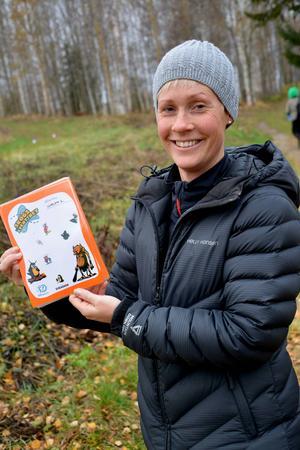 Anette Bergman, idrottslärare, visar upp arket som barnen ska fylla med klistermärken för varje lyckat uppdrag.