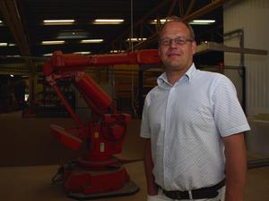Lysande tider. Niklas Johansson berättar att det går mycket bra för Leksandsdörren just nu. Bakom sig har han en av robotarna i fabriken. Företaget producerar 9000 ytterdörrar per år. Foto:Göran Persson