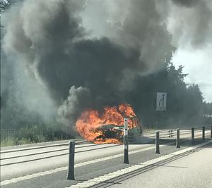 En bil fattade eld mitt på riksväg 70 i södergående körfält.